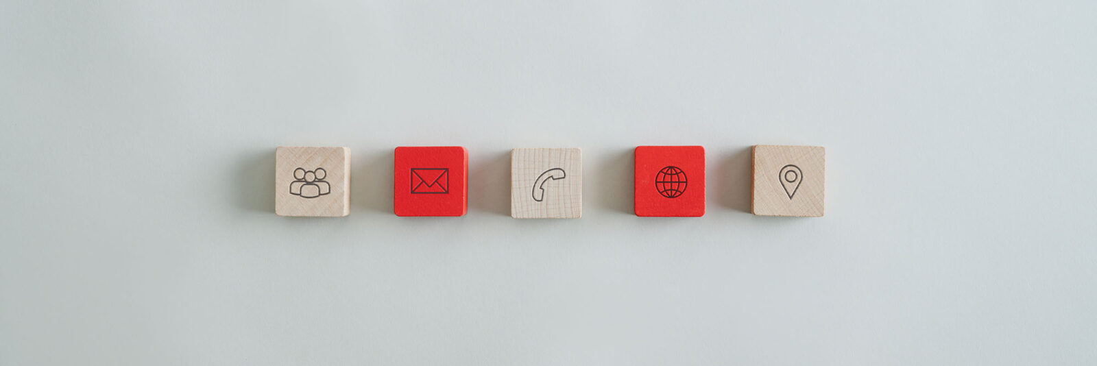 Wide view image of five wooden blocks with contact and information icons placed over grey background.